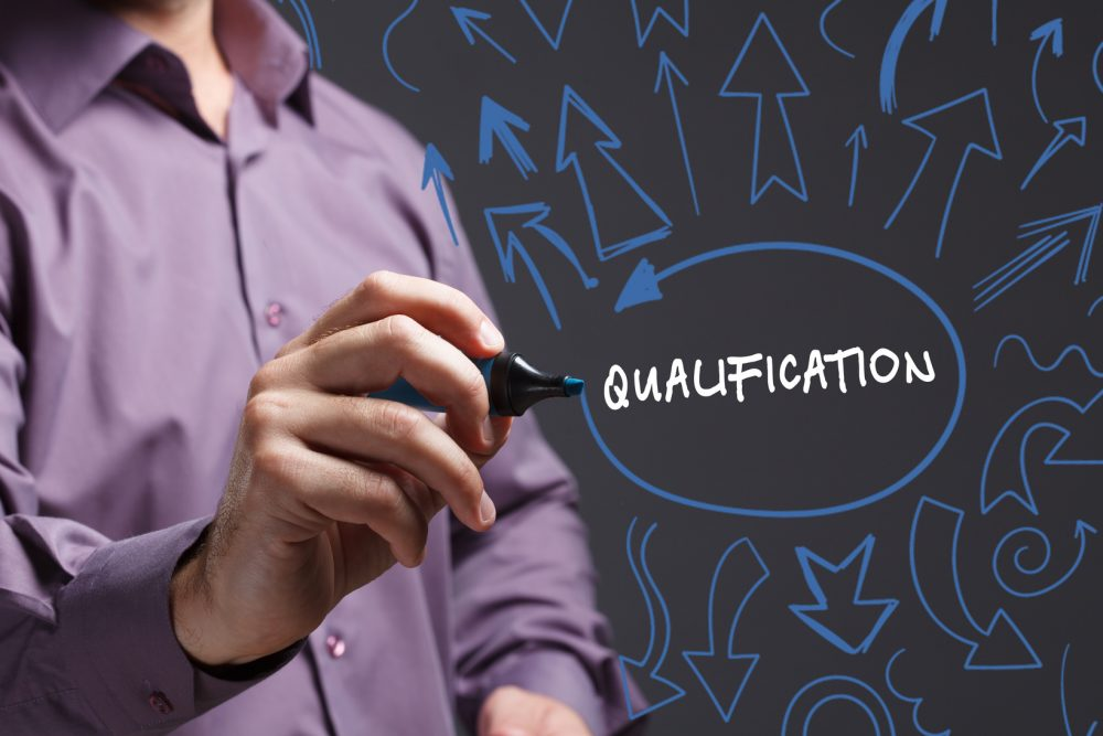 Technology, internet, business and marketing. Young business man writing word: qualification